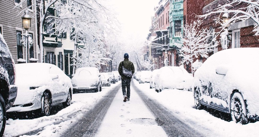 person walking down snow covered Boston street